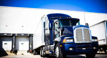 Milestone Trailer Leasing - Blue Transport truck docking at warehouse